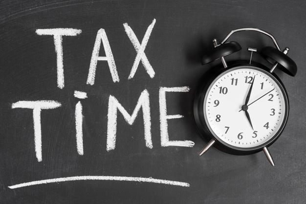 alarm-clock-near-tax-time-word-written-black-backboard-with-chalk_23-2147943569